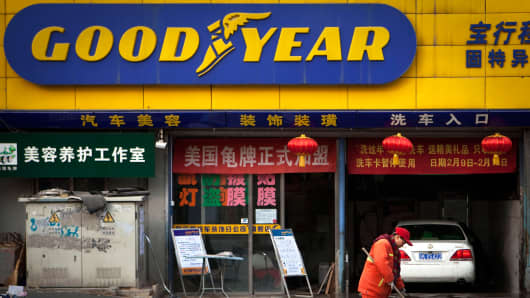 A cleaner works in front of a Goodyear retail shop in Beijing.