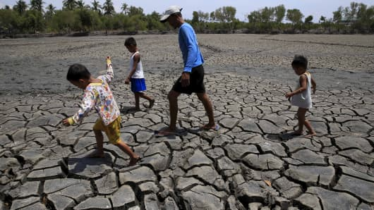 A father with his children walk over the cracked soil of a 1.5 hectare dried up fishery at the Novaleta town in Cavite province, south of Manila. The drought-inducing El Nino weather phenomenon continue to affect farmlands in the provinces resulting to more damaged crops.
