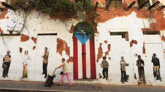 A woman walks by a rundown building on in Old San Juan, Puerto Rico.