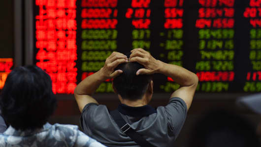 An investor looks at screens showing stock market movements at a securities company in Beijing.