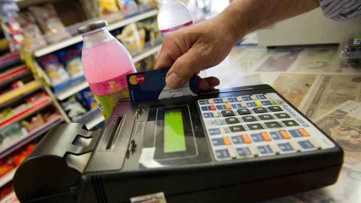 A merchant slides a credit card for a transaction.