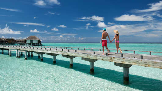 Couple on a tropical beach jetty at Maldives.