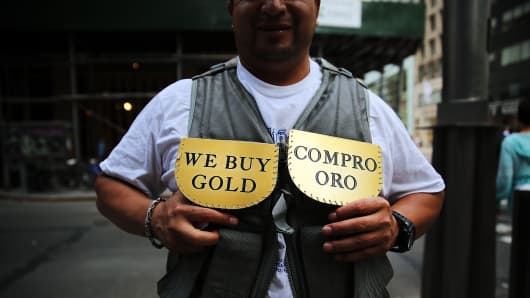 A man advertises for a jewelry store that buys gold in Manhattan in New York City.