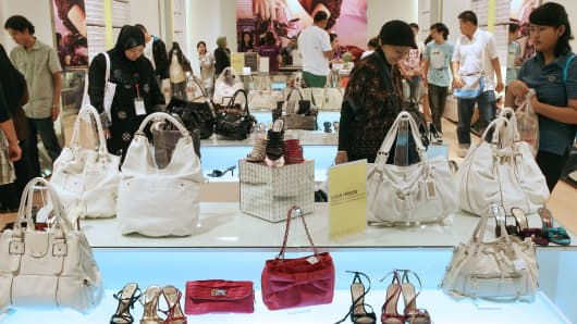 Shoppers look at a display of shoes and handbags at a store in Kuala Lumpur, Malaysia.