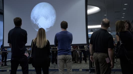 People look at an image of Pluto taken by the New Horizons probe as the craft makes its closest flyby of the dwarf planet at the Johns Hopkins University Applied Physics Laboratory on July 14, 2015, in Laurel, Maryland.