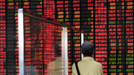An investor looks at screens showing stock market movements at a brokerage house in Shanghai.