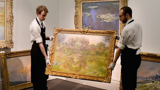 Gallery technicians carry Claude Monet's 'Bassin aux nympheas, les rosiers', 1913, from a collection of six pieces of the artist's work which are going on show at Sotheby's on April 10, 2015 in London, England.