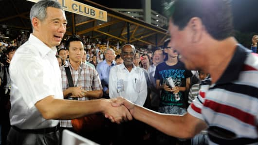 Singapore Prime Minister Lee Hsien Loong (L) shaking hands with a PAP supporter during a May election rally.