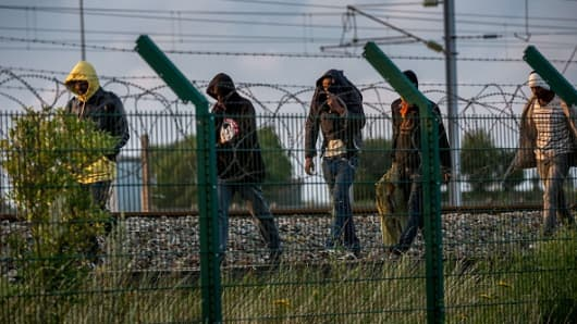 Migrants who successfully crossed the Eurotunnel terminal walk on the side of the railroad as they try to reach a shuttle to Great Britain.