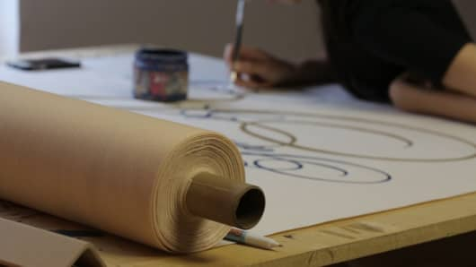 The Original Runner Company artist painting a wedding runner to be placed underfoot at a wedding ceremony.