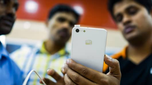 A store assistant, right, demonstrates a Micromax Informatics Ltd. smartphone to customers at the company's Micromax World store in New Delhi, India.