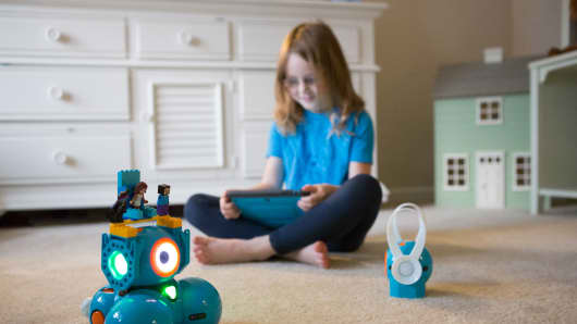 A young girl playing with Wonder Workshop's Dash & Dot robots.