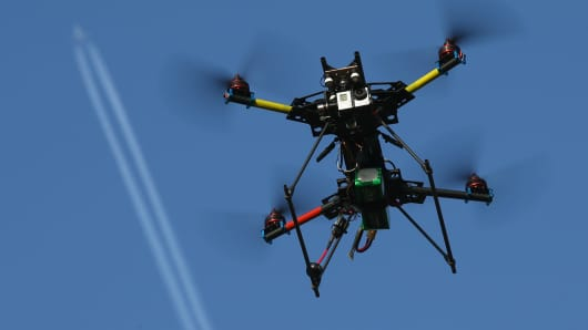 A commercial passenger plane flies overhead as a multirotor quadcopter drone is used for aerial photography.