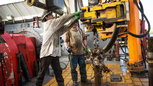Workers with Raven Drilling line up pipe while drilling for oil in the Bakken shale formation outside Watford City, North Dakota.