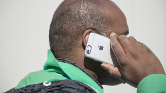 Man talks on his iPhone. Apple denies plans to sell mobile services directly to consumers.