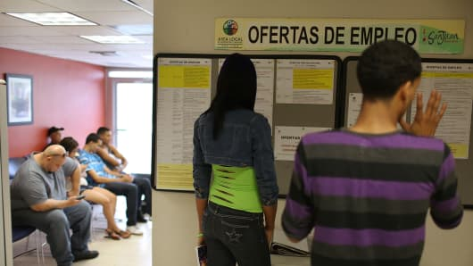 People look at the job listings posted at an unemployment office in San Juan, Puerto Rico.