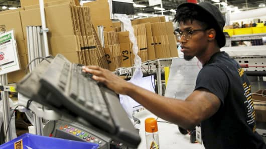 A worker prepares packaged products for shipment at an Amazon Fulfilment Center in Tracy, California.