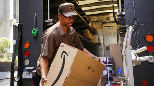 A UPS worker carries an Amazon box to be delivered in New York in July.