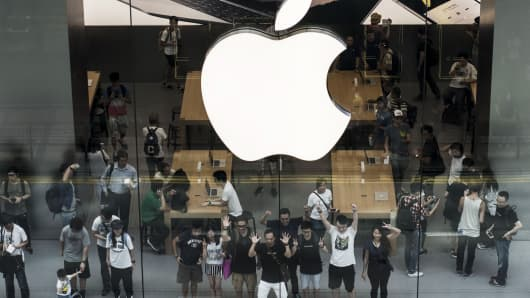 Customers pose for a photograph inside Apple Inc.'s new Canton Road store in the Tsim Sha Tsui district of Hong Kong, China, on Thursday, July 30, 2015.