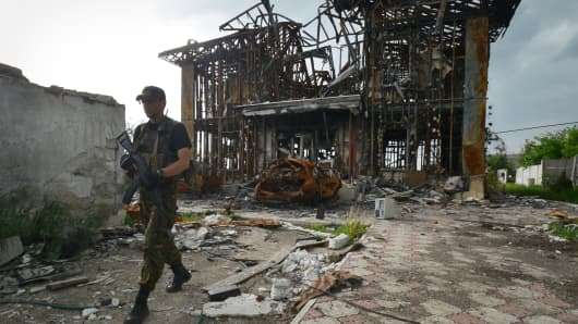 A serviceman walks in front of a destroyed house near Donetsk in eastern Ukraine.