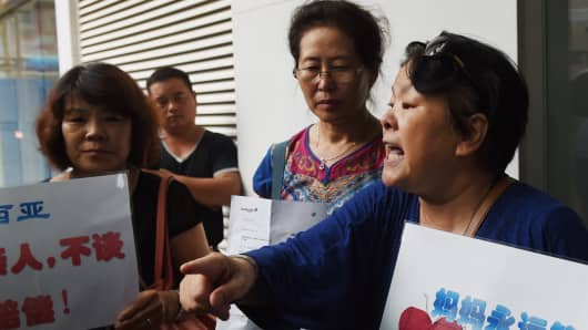 Relatives of passengers on missing Malaysia Airlines MH370 speak outside the Malaysia Airlines office in Beijing, expressing anger and disbelief after Malaysia's prime minister said wreckage found on a French Indian Ocean island was from the plane.