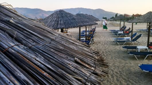 A holidaymaker passes rows of empty sunloungers and parasols on a beach at a tourist resort in Asprovalta, Greece, on Sunday, July 12, 2015.