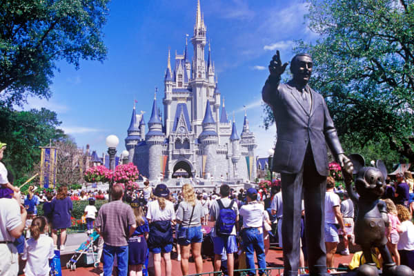 Walt Disney statue and the Magic Kingdom in Orlando, Florida.