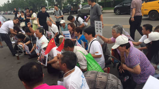 The family members of MH370 passengers kneel in front of foreign media gathered outside the Beijing office of Malaysia Airlines.