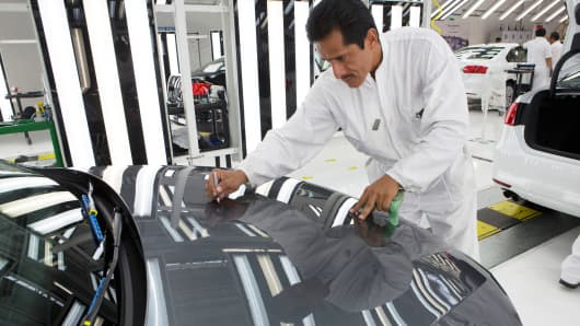 An employee inspects a Volkswagen Jetta at the company's assembly plant in Puebla, Mexico.
