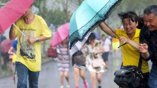 People hold umbrellas in heavy rain as Typhoon Soudelor approaches, in Hangzhou, China, August 7, 2015.