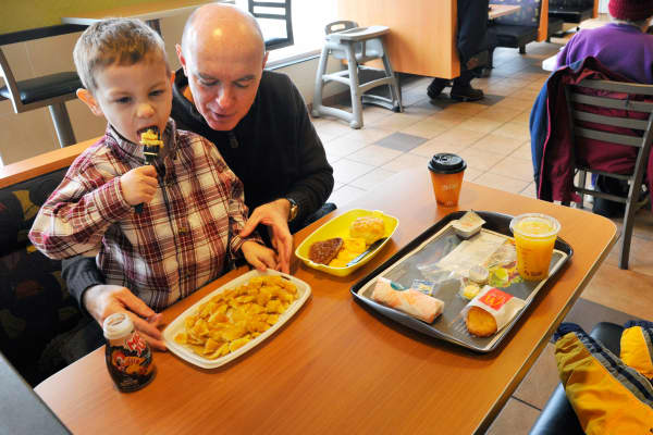 A father and son eating breakfast at McDonald's.