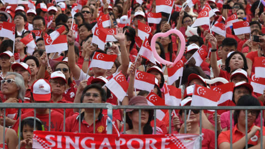 People wave national flags during Singapore's 50th National day anniversary celebration at the Padang in Singapore.