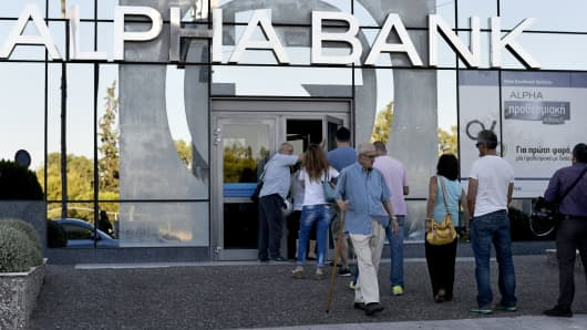 People wait to enter a bank in Athens.