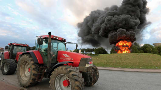 Tractors are parked around a roundabout with a fire burning during demonstration by dairy farmers in Ghislenghien, Belgium.