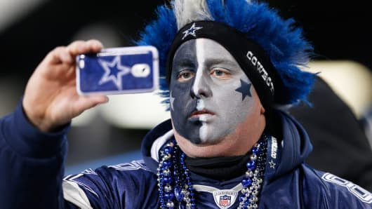 A Dallas Cowboys fan takes a photo with his cell phone last December in Chicago.