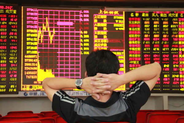 A man observes stock market prices at an exchange hall in Haikou, China.