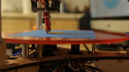 A build-it-yourself 3-D printer made by Deltaprintr prints a three-dimensional object made of plastic.