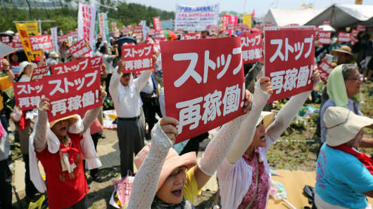 Anti-nuclear protesters holding a rally against the restart of a nuclear reactor in front of the Kyushu Electric Power Sendai nuclear power plant.