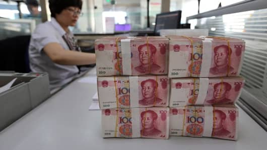 Renminbi banknotes are placed on a bank staff's table in a bank in Lianyungang, east China's Jiangsu province