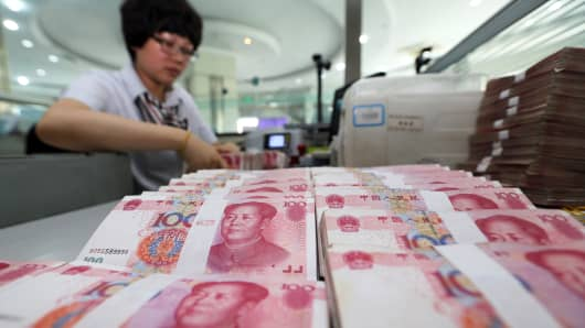 A teller counts yuan bank notes in a bank in Lianyungang, China.
