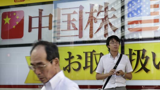 Pedestrians stand in front of an electronic board displaying an advertisement for Chinese stocks outside a securities firm in Tokyo, Japan, on Tuesday, Aug. 11, 2015.