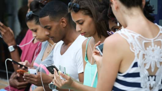 Young Cubans on mobile devices in Havana, Cuba.