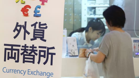 A woman trades money at a currency exchange at Haneda Airport in Tokyo, Aug. 12, 2015.