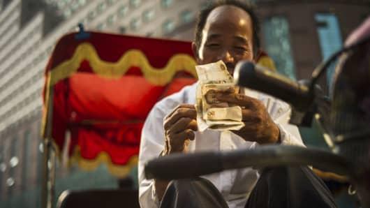 A man checks Chinese yuan bills in Beijing.