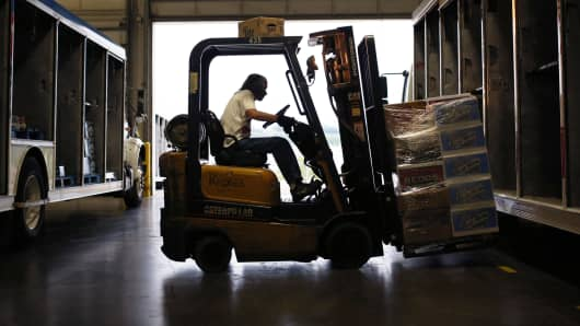 A worker uses a forklift to load a delivery truck with MillerCoors beverages at the Stagnaro Distributing facility in Cincinnati, Ohio.