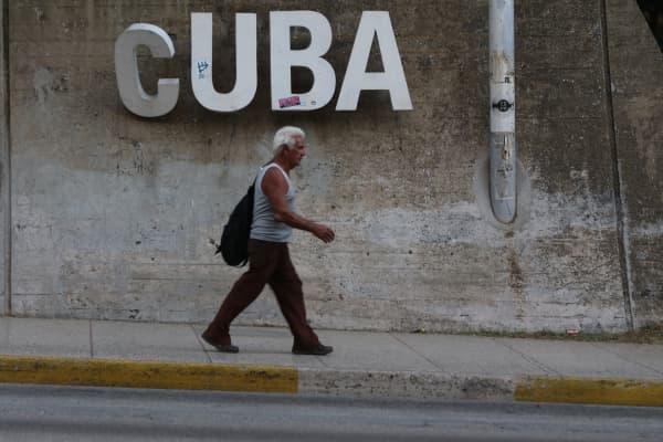 A man walks down a street in Havana, Cuba.