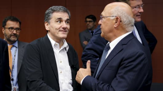 Greek Finance Minister Euclid Tsakalotos listens his French counterpart Michel Sapin (R) during a euro zone finance ministers meeting in Brussels, Belgium, August 14, 2015. Euro zone finance ministers will discuss whether to agree a third bailout package for Greece on Friday at their meeting in Brussels after the Greek parliament voted to approve the terms.