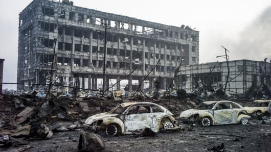 Burnt out Volkswagen cars are pictured amongst the damage on the second morning after a series of explosions at a chemical warehouse hit the city of Tianjin, in northern China on August 14, 2015.