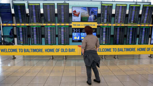 A traveler looks at the board of delayed and cancelled flights in the Southwest Airlines terminal at Baltimore/Washington International Thurgood Marshall Airport.