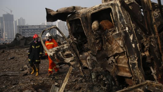 Firefighters walk past a damaged truck at the site of the explosions in Tianjin on August 15, 2015.
